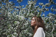 Portrait of a beautiful young woman posing by a cherry tree out in nature - INGF10751