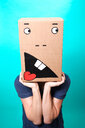 A person holding a cardboard box over their head indoors - INGF10763