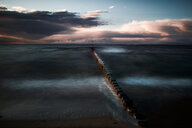 Scenic view of the sea under dark clouds during sunset - INGF10772
