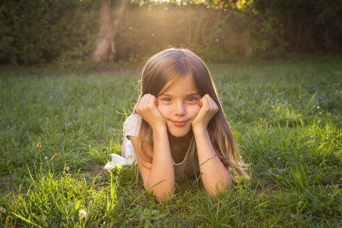 Portrait of little girl lying on a meadow at evening twilight - LVF07609