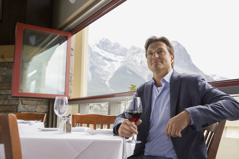 Businessman drinking wine at table on balcony - HEROF01199