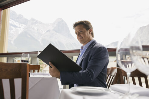 Businessman reading menu at table on balcony - HEROF01202
