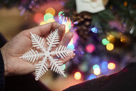 Woman's hand holding Christmas ornament, close-up - BZF00472