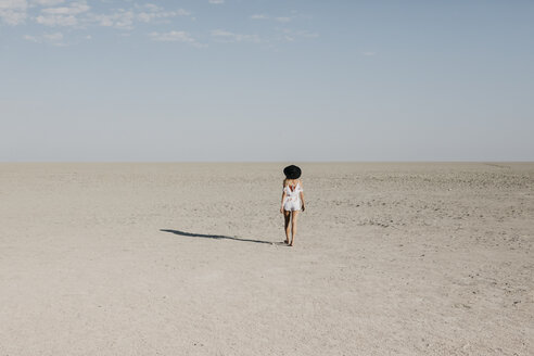 Woman with black hat, walking in the desert - LHPF00205