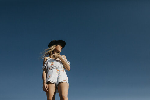Woman wearing a black hat standing against blue sky - LHPF00214