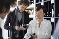 Sommelier recommending bottle to couple in wine store - HEROF01300