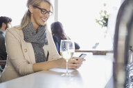 Woman drinking white wine and texting at bar - HEROF01339