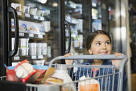 Girl pushing shopping cart in market - HEROF01465