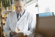 Pharmacist looking at label on box in market - HEROF01477