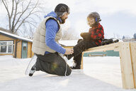 Father tying ice-skates for son - HEROF01501