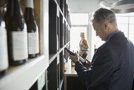 Man reading label on bottle in wine store - HEROF01516