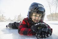 Portrait of boy lying on ice hockey rink - HEROF01522