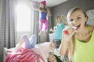Girl singing into hairbrush at slumber party - HEROF01612