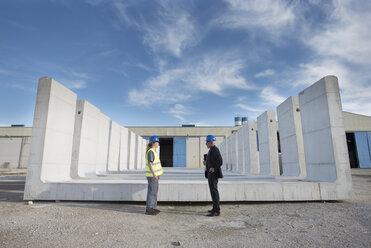 Businessman and female worker standing on industrial site in front of concrete blocks - JASF02026
