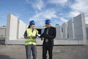 Businessman talking with female worker on industrial site in front of concrete blocks - JASF02029