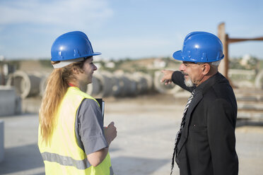 Businessman talking with female worker on industrial site - JASF02038