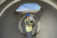 Portrait of smiling female worker standing inside concrete pipe on industrial site - JASF02041