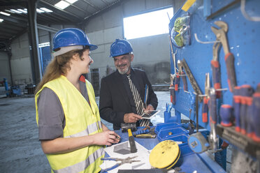 Smiling businessman talking with female worker in factory - JASF02047