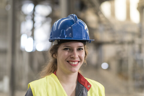 Portrait of smiling female worker wearing hard hat standing in a factory - JASF02053