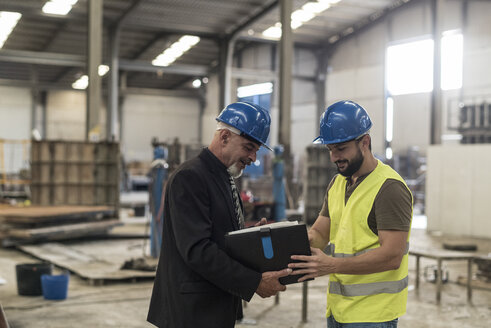 Businessman with folder talking to worker in factory - JASF02056