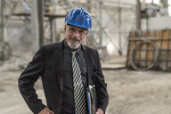 Portrait of confident businessman wearing hard hat standing in a factory - JASF02059
