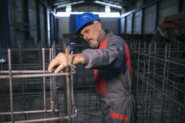 Worker wearing hard hat in factory checking rebar - JASF02062