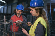 Male and female worker wearing hard hats working on rebar in factory - JASF02065