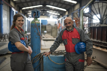 Portrait of confident male and female worker in factory - JASF02068