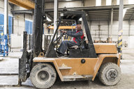 Worker driving forklift in factory - JASF02071
