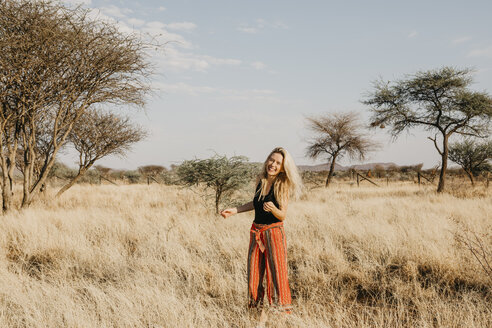 Africa, Namibia, blonde smiling woman standing in grassland - LHPF00223