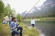 Family fishing at lakeside below mountains - HEROF01717