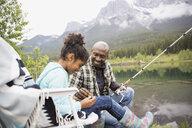Father teaching daughter to fish at lakeside - HEROF01723