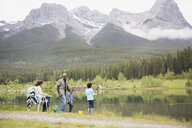 Family fishing at lakeside below mountains - HEROF01729