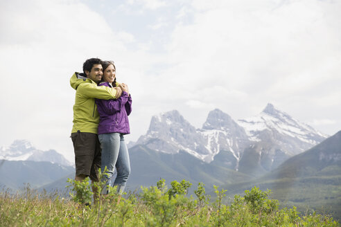 Couple hugging in field near mountains - HEROF01750