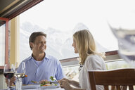 Couple eating at restaurant table on balcony - HEROF01759