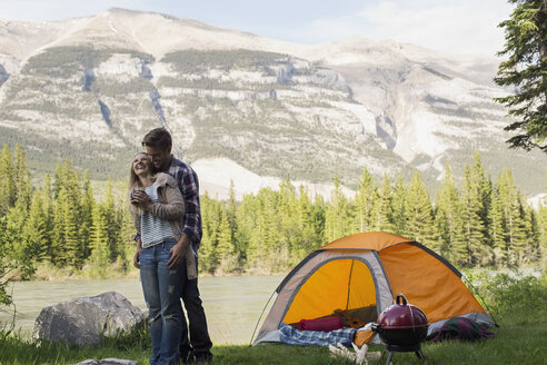 Couple hugging outside campsite at lakeside - HEROF01768