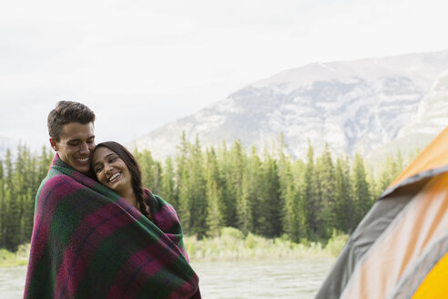 Couple wrapped in blanket at campsite - HEROF01774