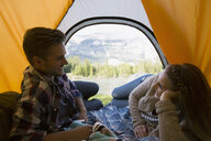 Couple laying in tent with mountain view - HEROF01777