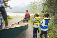 Family carrying canoe toward lake - HEROF01789