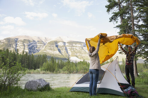 Couple assembling tent at campsite near mountains - HEROF01792