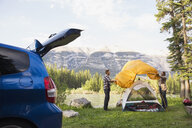 Couple assembling tent at campsite near mountains - HEROF01795