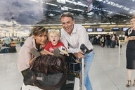 Family of three looking forward to their holiday at CGN airport, Cologne, NRW, Germany - MFF04720