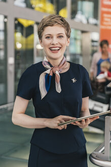 Portrait of happy airline employee holding tablet at the airport - MFF04723