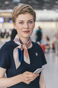 Portrait of confident airline employee holding cell phone at the airport - MFF04732