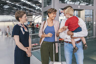 Family with small child speaking to member of ground crew at CGN airport, Cologne, NRW, Germany - MFF04735