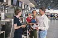 Family with small child speaking to member of ground crew at CGN airport, Cologne, NRW, Germany - MFF04747