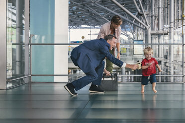 Happy child running around travelling business man at CGN airport, Cologne, NRW, Germany - MFF04756