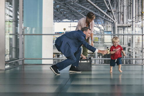 Happy child running around travelling businessman at the airport - MFF04756