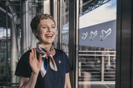 Happy airline employee waving out of the window at the airport - MFF04759