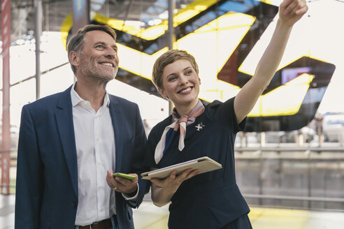 Smiling airline employee with tablet assisting businessman at the airport - MFF04768